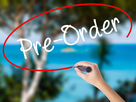 Woman Hand Writing Pre-Order  with black marker on visual screen. Isolated on nature. Business concept. Stock Photo