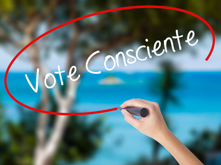 Woman Hand Writing Vote Consciente   (Vote conscientiously In Portuguese) with black marker on visual screen. Isolated on nature. Business concept. Stock Photo