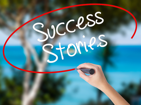 Woman Hand Writing Success Stories with black marker on visual screen. Isolated on nature. Business concept. Stock Photo