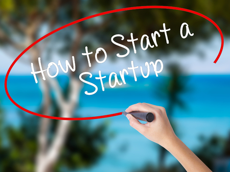 Woman Hand Writing How to Start a Startup with black marker on visual screen. Isolated on nature. Business concept. Stock Photo