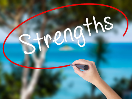 Woman Hand Writing Strengths with black marker on visual screen. Isolated on nature. Business concept. Stock Photo