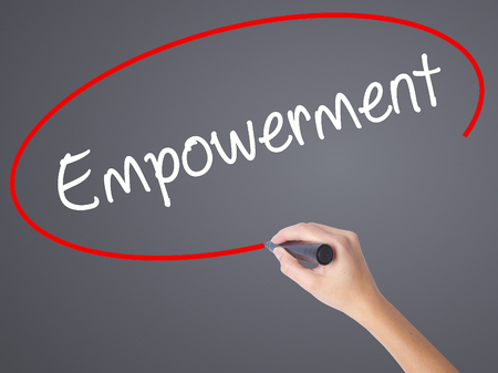 Woman Hand Writing Empowerment with black marker on visual screen. Isolated on grey. Business concept. Stock Photo
