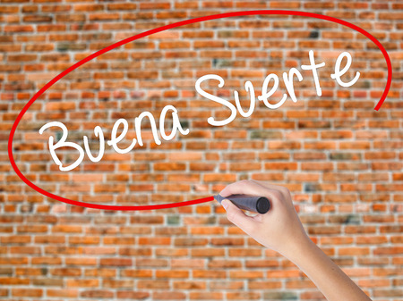 Woman Hand Writing Buena Suerte( Good Luck in Spanish) with black marker on visual screen. Isolated on bricks. Business concept. Stock Photo