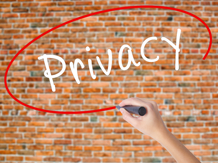 Woman Hand Writing Privacy with black marker on visual screen. Isolated on bricks. Business concept. Stock Photo