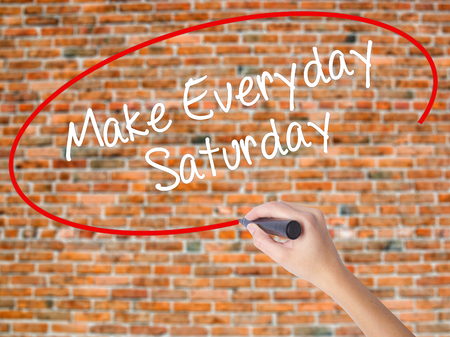 Woman Hand Writing Make Everyday Saturday with black marker on visual screen. Isolated on bricks. Business concept. Stock Photo