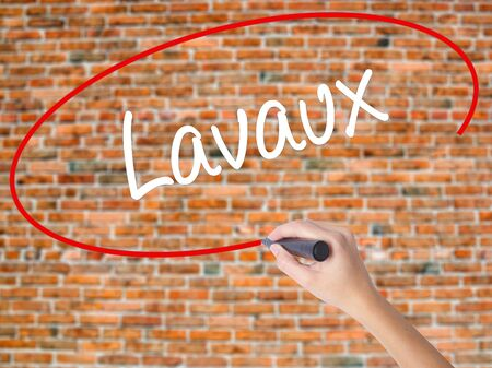 Woman Hand Writing Lavaux  with black marker on visual screen. Isolated on bricks. Business concept. Stock Photo