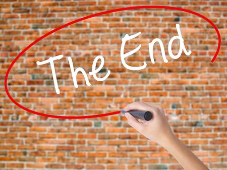 Woman Hand Writing The End with black marker on visual screen. Isolated on bricks. Business, technology, internet concept. Stock Photo
