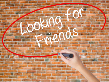 Woman Hand Writing Looking for Friends with black marker on visual screen. Isolated on bricks. Business concept. Stock Photo