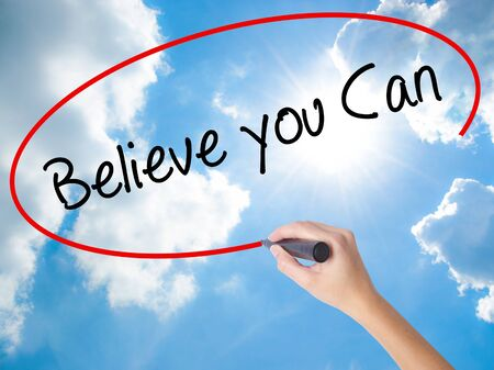 Woman Hand Writing Believe you Can with black marker on visual screen. Isolated on Sunny Sky. Business concept. Stock Photo