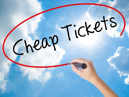 Woman Hand Writing Cheap Tickets with black marker on visual screen. Isolated on Sunny Sky. Business concept. Stock Photo