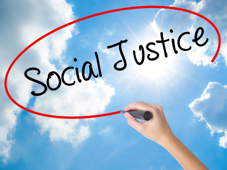 Woman Hand Writing Social Justice with black marker on visual screen. Isolated on Sunny Sky. Business concept. Stock Photo