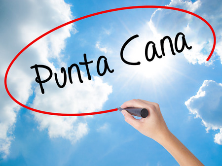 Woman Hand Writing Punta Cana with black marker on visual screen. Isolated on Sunny Sky. Business concept. Stock Photo