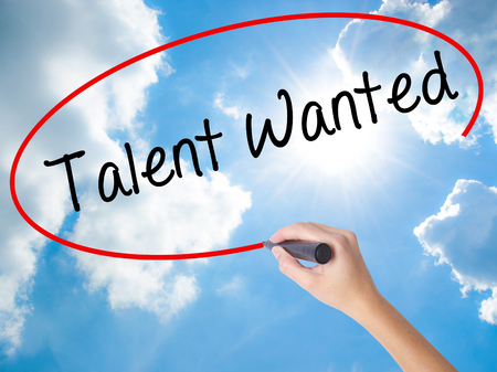 Woman Hand Writing Talent Wanted with black marker on visual screen. Isolated on Sunny Sky. Business concept. Stock Photo