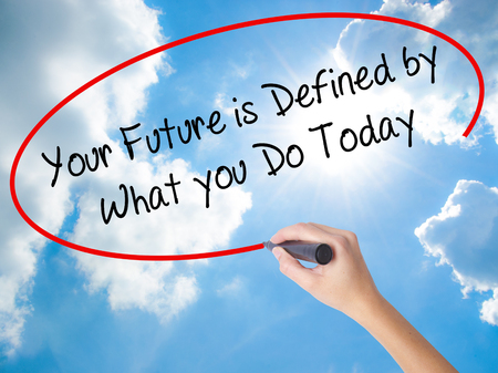 Woman Hand Writing Your Future is Defined by What you Do Today  with black marker on visual screen. Isolated on Sunny Sky. Business concept. Stock Photo