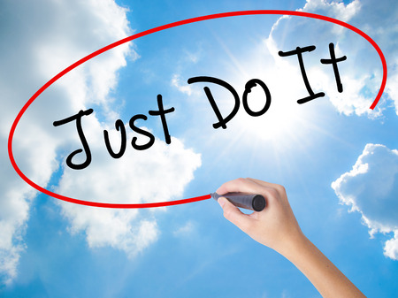 Woman Hand Writing Just Do It with black marker on visual screen. Isolated on Sunny Sky. Business concept. Stock Photo