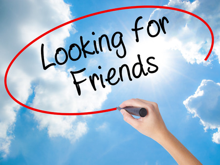 Woman Hand Writing Looking for Friends with black marker on visual screen. Isolated on Sunny Sky. Business concept. Stock Photo