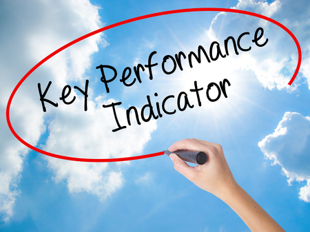 Woman Hand Writing Key Performance Indicator with black marker on visual screen. Isolated on Sunny Sky. Business concept. Stock Photo