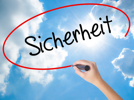 Woman Hand Writing Sicherheit (Safety in German) with black marker on visual screen. Isolated on Sunny Sky. Business,  internet concept. Stock Photo