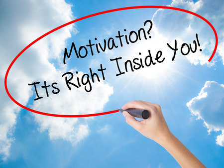 Woman Hand Writing Motivation? Its Right Inside You!  with black marker on visual screen. Isolated on Sunny Sky. Business concept. Stock Photo