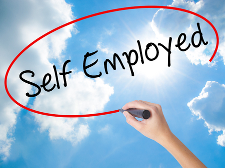 Woman Hand Writing Self Employed with black marker on visual screen. Isolated on Sunny Sky. Business concept. Stock Photo