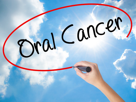Woman Hand Writing Oral Cancer  with black marker on visual screen. Isolated on Sunny Sky. Business concept. Stock Photo