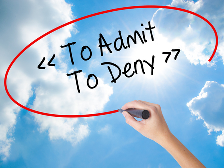 Woman Hand Writing To Admit - To Deny with black marker on visual screen. Isolated on Sunny Sky. Business concept. Stock Photo
