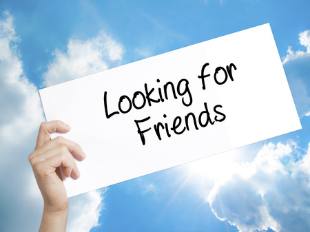 Man Hand Holding Paper with text Looking for Friends . Sign on white paper. Isolated on Sky background.  Business concept. Stock Photo
