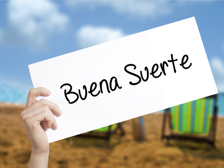 Buena Suerte( Good Luck in Spanish) Sign on white paper. Man Hand Holding Paper with text. Isolated on holiday background.   Business concept. Stock Photo