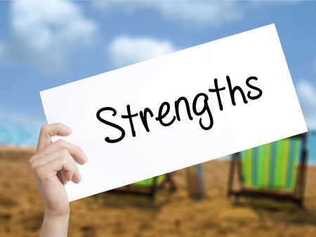 Strengths Sign on white paper. Man Hand Holding Paper with text. Isolated on holiday background.  Business concept. Stock Photo