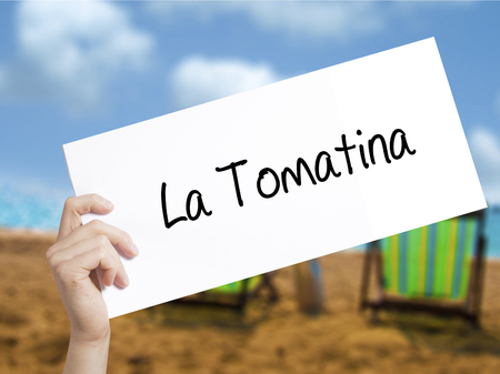La Tomatina Sign on white paper. Man Hand Holding Paper with text. Isolated on holiday background.  technology, internet concept.