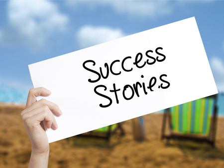 Success Stories Sign on white paper. Man Hand Holding Paper with text. Isolated on holiday background.   Business concept. Stock Photo