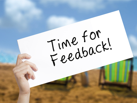 Time for Feedback Sign on white paper. Man Hand Holding Paper with text. Isolated on holiday background.  Business concept. Stock Photo
