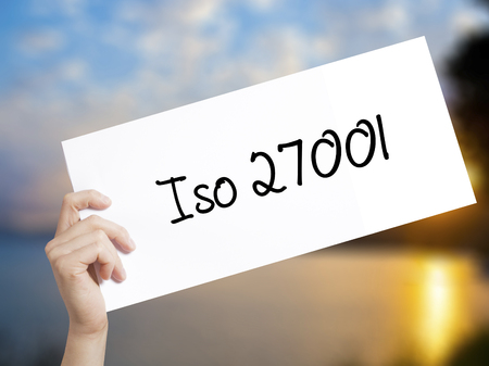 Iso 27001  Sign on white paper. Man Hand Holding Paper with text. Isolated on sunset background.   Business concept. Stock Photo