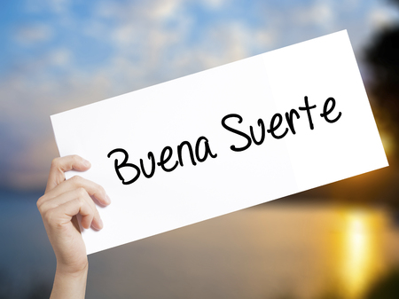 Buena Suerte( Good Luck in Spanish) Sign on white paper. Man Hand Holding Paper with text. Isolated on sunset background.   Business concept. Stock Photo