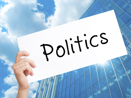 Politics Sign on white paper. Man Hand Holding Paper with text. Isolated on Skyscraper background.  Business concept. Stock Photo