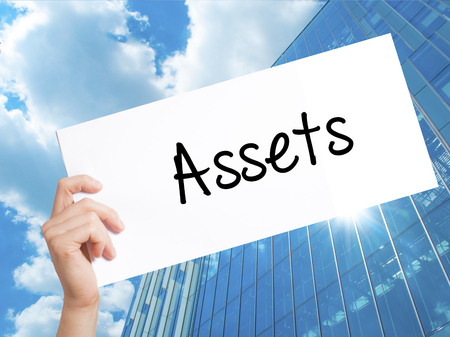 Assets Sign on white paper. Man Hand Holding Paper with text. Isolated on Skyscraper background.   Business concept. Stock Photo