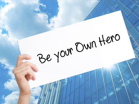 Be your Own Hero  Sign on white paper. Man Hand Holding Paper with text. Isolated on Skyscraper background.   Business concept. Stock Photo