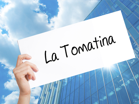 La Tomatina Sign on white paper. Man Hand Holding Paper with text. Isolated on Skyscraper background.  technology, internet concept.