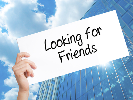 Looking for Friends Sign on white paper. Man Hand Holding Paper with text. Isolated on Skyscraper background.  Business concept. Stock Photo