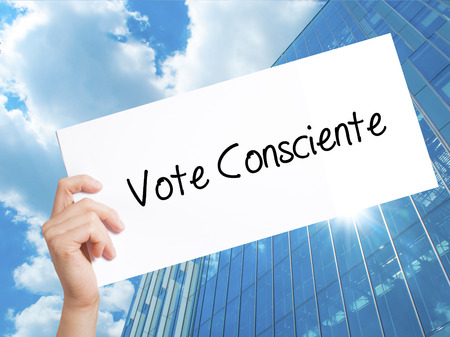 Vote Consciente   (Vote conscientiously In Portuguese) Sign on white paper. Man Hand Holding Paper with text. Isolated on Skyscraper background.  Business concept. Stock Photo