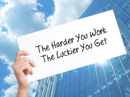 The Harder You Work The Luckier You Get  Sign on white paper. Man Hand Holding Paper with text. Isolated on Skyscraper background.  technology, internet concept.