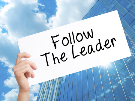Follow The Leader Sign on white paper. Man Hand Holding Paper with text. Isolated on Skyscraper background.  Business concept. Stock Photo