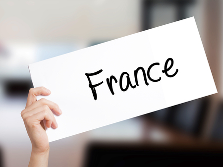 France Sign on white paper. Man Hand Holding Paper with text. Isolated on Office background.   Business concept. Stock Photo