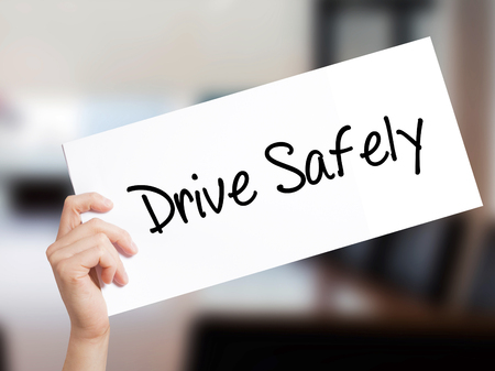 Drive Safely Sign on white paper. Man Hand Holding Paper with text. Isolated on Office background.   Business concept. Stock Photo