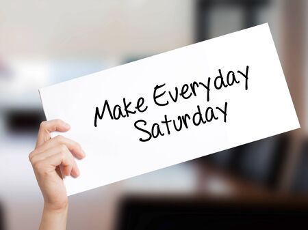 Make Everyday Saturday Sign on white paper. Man Hand Holding Paper with text. Isolated on Office background.  Business concept. Stock Photo