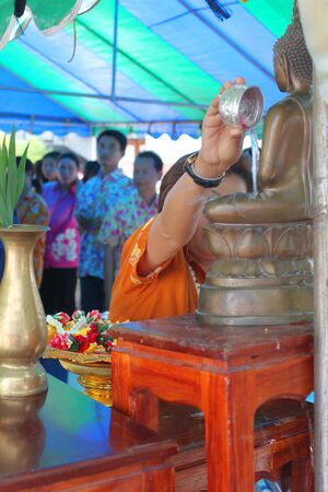 MUANG, MAHASARAKHAM - APRIL 11 : Muang District Director' s wife is pouring water on Buddha image for merit in Thai New Year or Songkran Festival on April 11, 2013 at District Director House, Muang, Mahasarakham, Thailand.