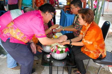 MUANG, MAHASARAKHAM - APRIL 11 : Unidentified people are pouring water for greeting and asking Distric Director and his wife for blessing in Thai New Year or Songkran Festival on April 11, 2013 at District Director House, Muang, Mahasarakham, Thailand.