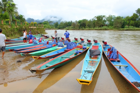 VANG VIENG, LAO P D R  - AUGUST 24   Unidentified men are preparing completion for tourists to take long-tailed boat tour in Song River on August 24, 2013 in Vang Vieng, Lao P D R
