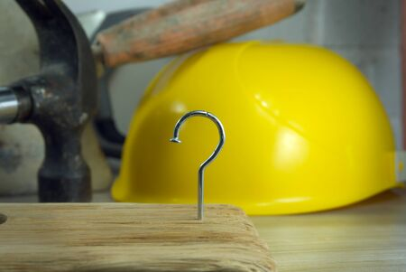 Photo pour Construction nail shaped as question mark with blurred background of various tools and helmet, construction questions and confusion concept - image libre de droit
