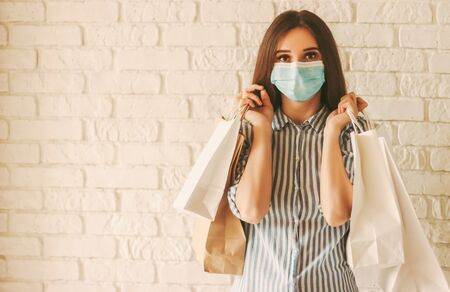 Photo pour Happy girl shopper in protective face mask with paper bags in hands. Young woman in medical face mask holding shopping bags. Girl shopaholic in mall. Sale, discount, coronavirus COVID-19, copy space - image libre de droit